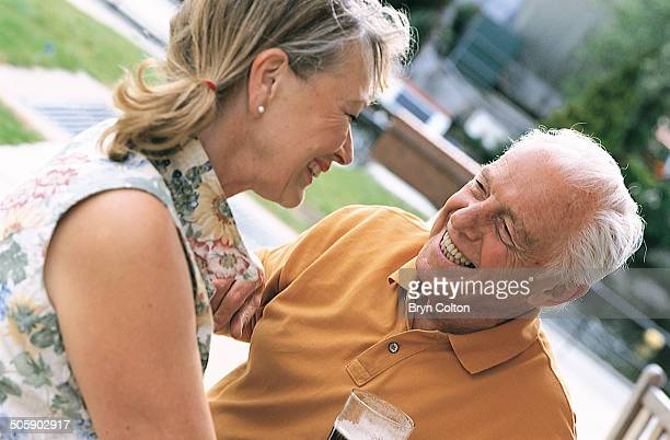 An elderly couple sit outside and enjoy a drink at a local bar in this arranged photograph taken in the Riverside area of Norwich Norfolk in May 2000