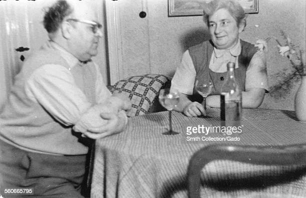 An elderly couple sitting at a dining table drinking a glass of wine Germany 1949