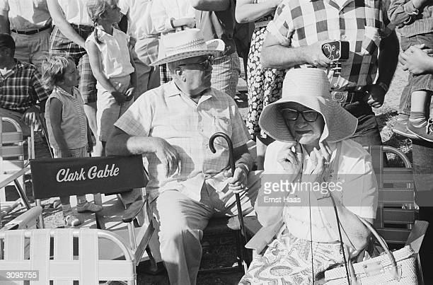 An elderly couple sitting by the chair reserved for Clark Gable on the set of 'The Misfits' filming on location in the Nevada Desert