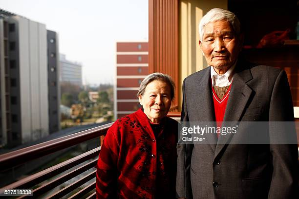 An elderly couple stands on the balcony of their apartment at the CherishYearn retirement community on the outskirts of Shanghai China on Tuesday Dec...