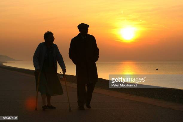 An elderly couple stroll on the sea front in early morning on September 28 2008 in Hythe England
