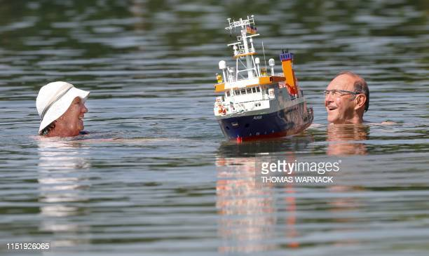 An elderly couple swim past a model boat at the Schwarzachtalsee lake in Ertingen, southern Germany, on June 26, 2019. - As Europe sizzled at the...
