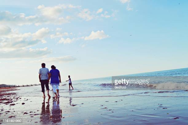 an elderly couple taking a walk by the sea on a sandy beach, as a young boy looks back at them - old man feet stock pictures, royalty-free photos & images