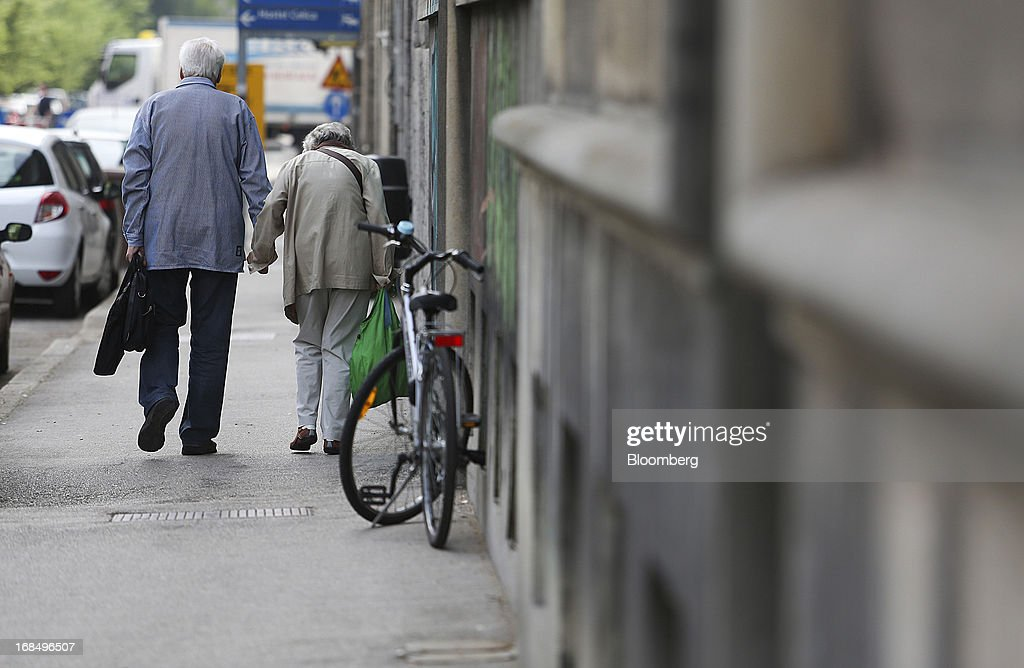An elderly couple walk along a street in Ljubljana, Slovenia, on Friday, May 10, 2013. The Adriatic nation is seeking to fix its ailing lenders with a cash injection of at least 900 million euros ($1.17 billion) after Cyprus's bailout focused investors on countries with weak banking industries. Photographer: Chris Ratcliffe/Bloomberg via Getty Images