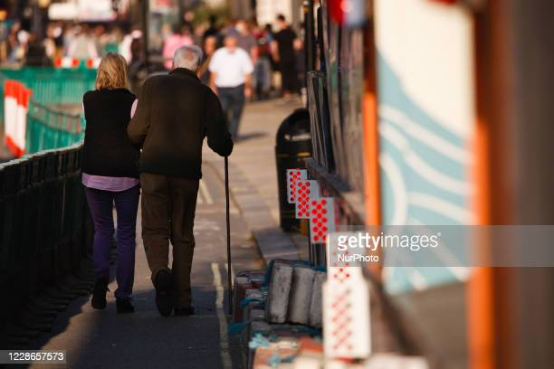 An elderly couple walk along Piccadilly within temporary pavement barriers installed to aid social distancing in London, England, on September 22,...