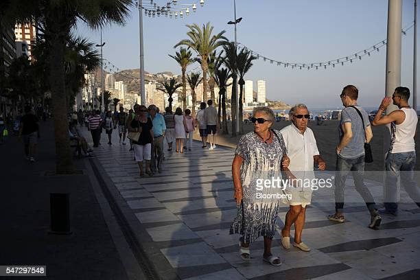 An elderly couple walk along the beachfront promenade with holidaymakers in Benidorm Spain on Tuesday July 12 2016 Spain registered record tourism...