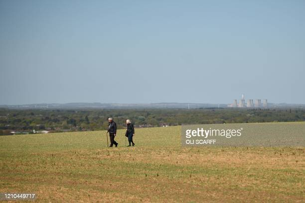 An elderly couple walk in the countryside near Lincoln in Eastern England on April 20 as life in Britain continues during the nationwide lockdown to...