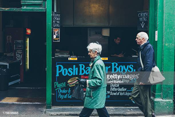 An elderly couple walk past a fast food stall in Borough market.