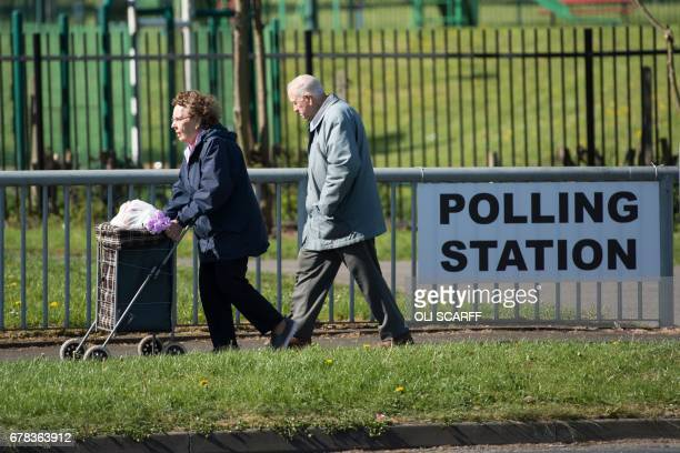An elderly couple walk past a sign for a polling station in Manchester northern England on May 4 2017 Voting began today in Britain's local elections...