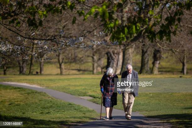 An elderly couple walk through Greenwich Park in London, U.K., on Saturday, April 4, 2020. The U.K. Reported its deadliest day yet, with an increase...