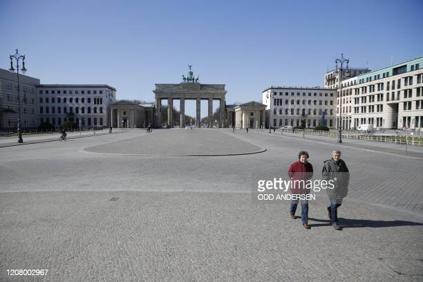 An elderly couple walks across the deserted Pariser Platz by the Brandenburg Gate in Berlin on March 23 amid the new coronavirus COVID-19 pandemic.