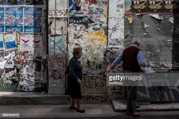 An elderly couple walks in Central Athens in front of closed shops on May 8 2017 Greece reached an agreement with its lenders during last week The...