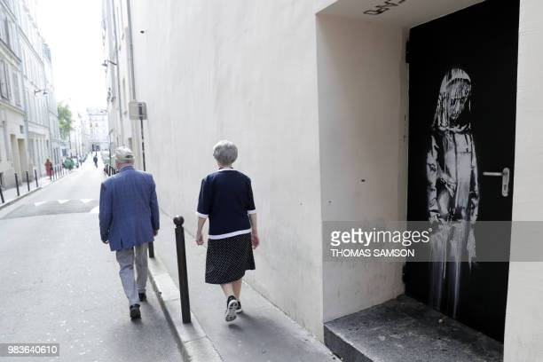 An elderly couple walks past a recent artwork by street artist Banksy in Paris on June 25 on a side street to the Bataclan concert hall where a...