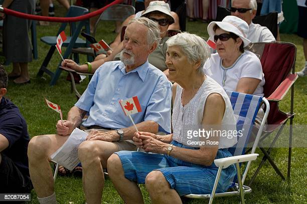 An elderly couple wave the Canadian maple leaf flag during Canada Day festivities in this 2008 Penticton British Columbia Canada summer photo Canada...