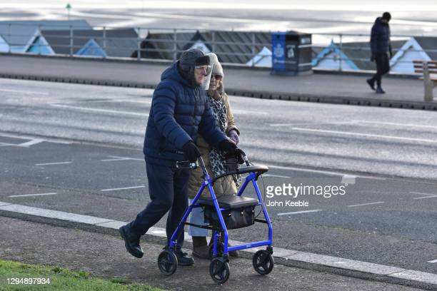 An elderly couple wear face sheilds as they take a walk along the seafront on January 06, 2021 in Southend, England. British MPs will vote...