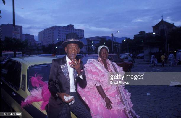 An elderly couple wearing costumes of Mangueira Samba School rests at dawn in the end of the samba schools parade, Rio de Janeiro carnival, Brazil.