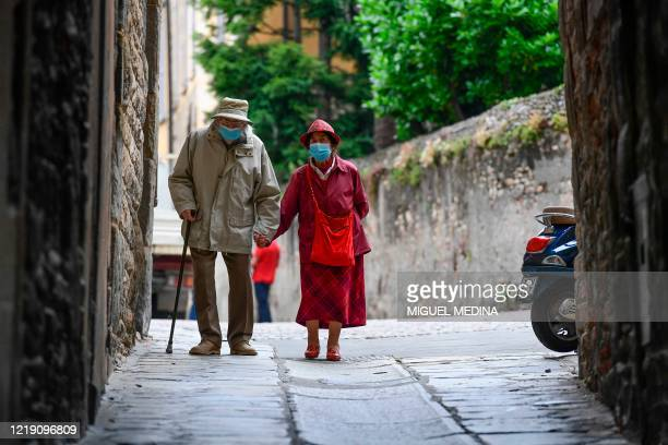 An elderly couple wearing face masks and holding hands walk in a street in the upper city of Bergamo on June 10 as Italy eases lockdown measures...