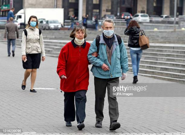 An elderly couple wearing face masks as a preventive measure walk on the street amid coronavirus crisis Ukraine's government Plans to introduce...