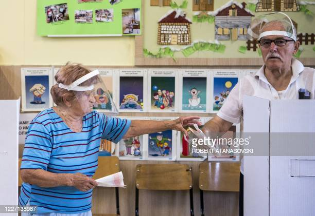An elderly couple wearing face shields cast their vote in a polling station during the general election in Skopje on July 15, 2020. - North Macedonia...