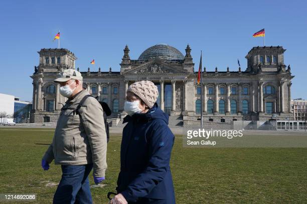 An elderly couple wearing protective masks and who said they did not mind being photographed walk past the Reichstag where inside the Bundestag is...