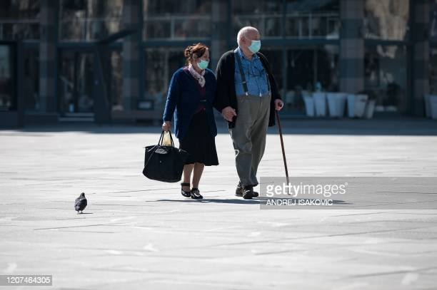An elderly couple wearing protective masks walks over Belgrade's main square on March 17, 2020. - Serbia's President said the new restrictions were...