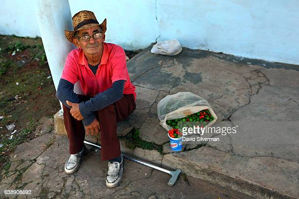 An elderly Cuban man supplements his pension by selling chili peppers outside a state food store on December 21 2015 in Vinales Cuba Cubans continue...
