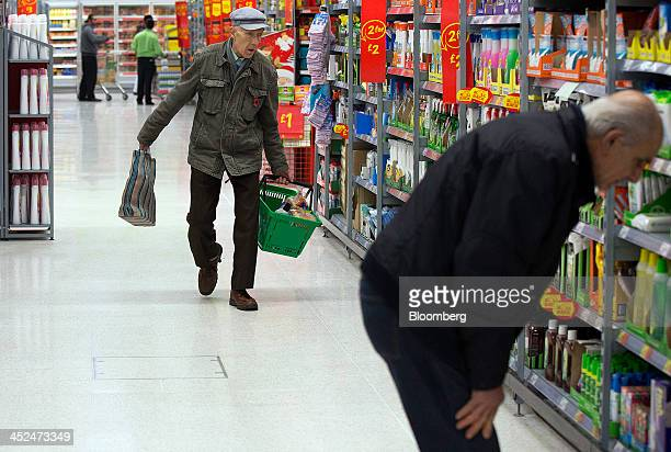 An elderly customer carries his groceries in a branded shopping basket as he shops for goods inside an Asda supermarket in Wembley London UK on...