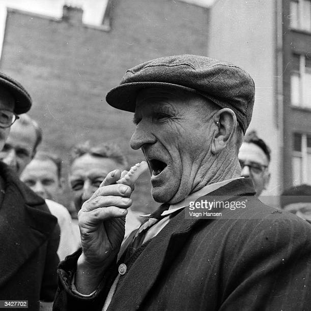 An elderly customer checks the fit of a set of dentures in the Waterlooplein marketplace Amsterdam There tradesman Gerard de Munnik sells second hand...