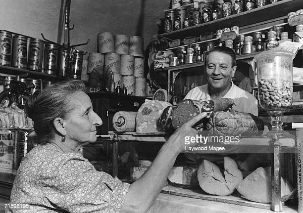 An elderly customer points to a selection of sausages in a grocer's shop Italy 1st November 1947 As well as food the shop also sells DDT insecticide...