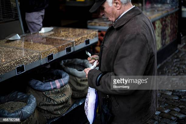 An elderly customer selects euro banknotes to pay for goods at a store selling nuts in Kapani market in Thessaloniki Greece on Monday April 6 2015...