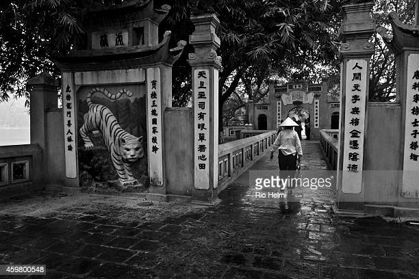 An elderly devotee makes her way through the entrance gate to Ngoc Son Temple on the Hoan KIem Lake in Hanoi Vietnam