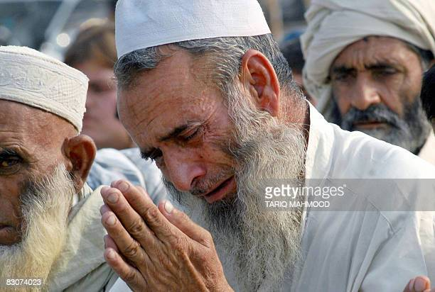 An elderly displaced Pakistani tribesman from the troubled district of Bajaur weeps as he offers 'Eid alFitr' prayers at a makeshift camp in Mardan...