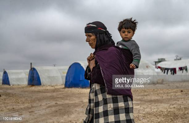TOPSHOT An elderly displaced Syrian woman carries a child in the Washukanni Camp for the internally displaced people near the predominantly Kurdish...