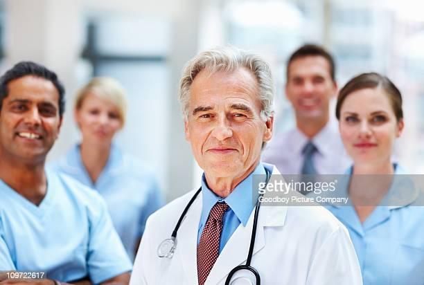 Ein älterer Arzt mit seinem team im Hintergrund verwischen