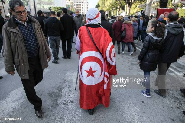 An elderly dressed in the Tunisian flag limps as she walks with a crutch during the celebrations of the 9th anniversary of the revolution held on...