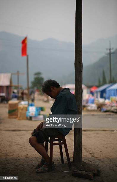 An elderly earthquake survivor falls asleep at a refugee camp on June 5, 2008 in Shifang, Sichuan province, China. More than 69,000 people are now...