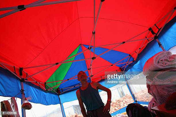 An elderly earthquake survivor stands inside a tent at a refugee camp on June 5, 2008 in Shifang, Sichuan province, China. More than 69,000 people...