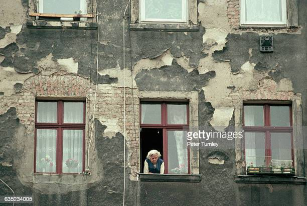 An elderly East German woman looks out the window of her dilapidated apartment