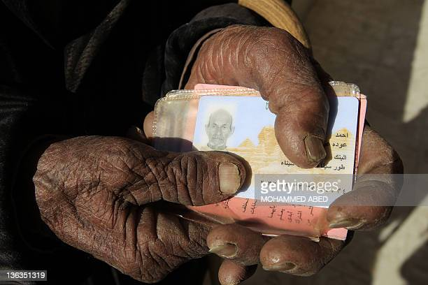 An elderly Egyptian man holds his ID card as he arrives to vote at a polling station in the Red Sea city of Sharm elSheikh during the third and final...