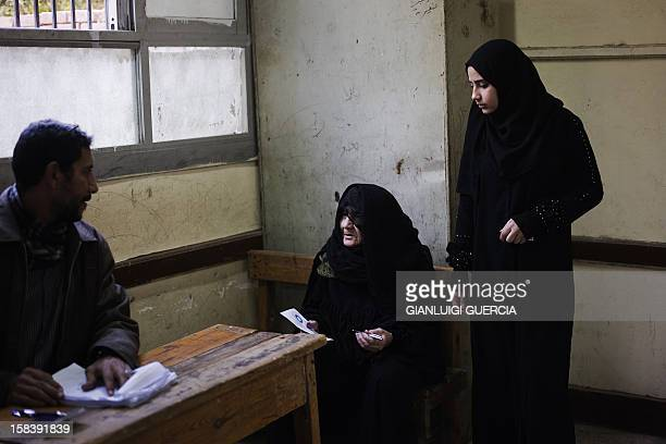 An elderly Egyptian woman speaks with a polling station official before marking her ballot during a referendum on a new constitution in President...