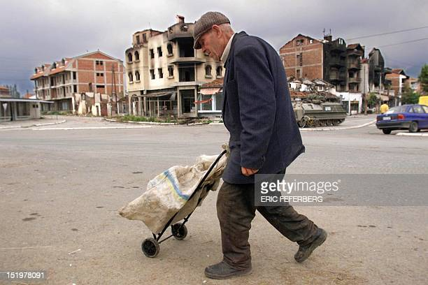 An elderly ethnic Albanian man walks in the streets of Pec southwestern Kosovo 14 June 1999 Serb forces are pursuing their withdrawal from Kosovo in...
