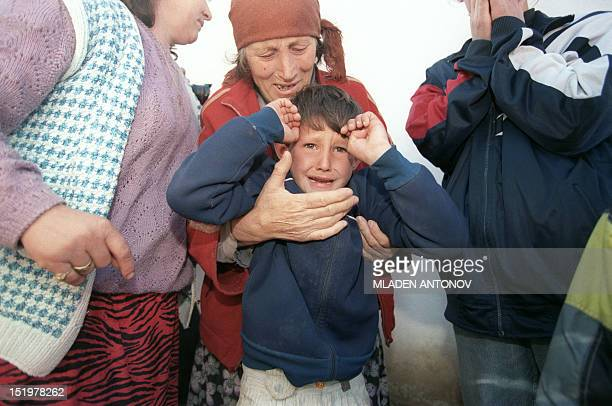 An elderly ethnic Albanian refugee woman from the village of Donje Prekaze cries holding her crying grandson as they hide from Serbian police in a...
