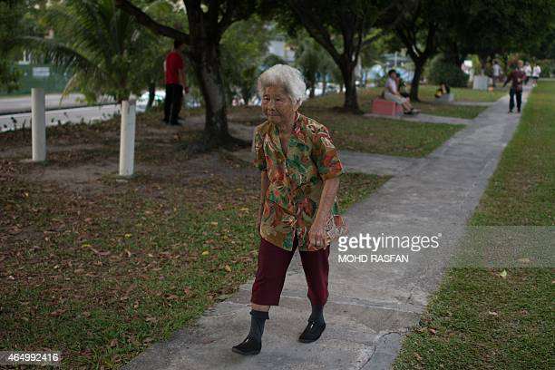 An elderly ethnic Chinese Malaysian woman walks in a park during her morning exercise in Kuala Lumpur on March 3 2015 AFP PHOTO / MOHD RASFAN