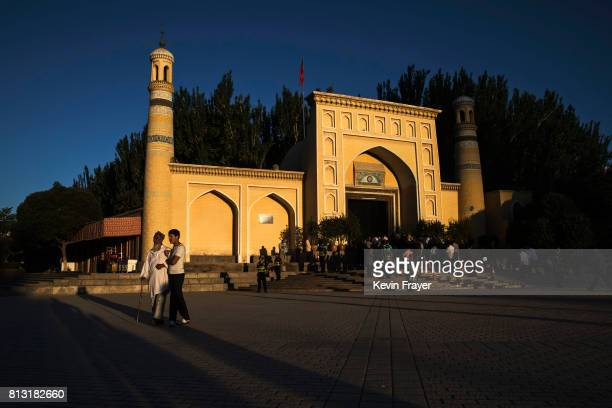 An elderly ethnic Uyghur man is helped before prayers marking Eid Al Fitr outside Id Kah Mosque on June 26 2017 in the old town of Kashgar in the far...