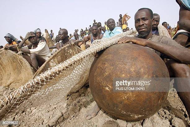An elderly fisherman sits with his colleagues at the bank of Argungu River in Argungu northwestern Nigeria on March 15 2008 to participate in the...