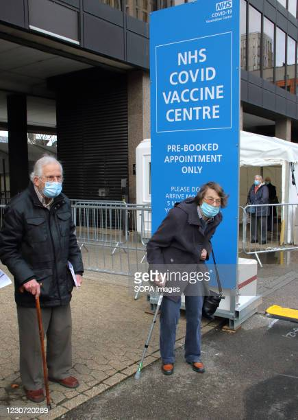 An elderly former nurse with her husband wearing face masks leave the vaccination centre after receiving their first dose of the Astra Zeneca Oxford...