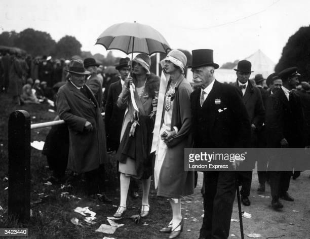 An elderly gentleman escorting two young women through the littered grouds of Ascot racecourse, Berkshire.