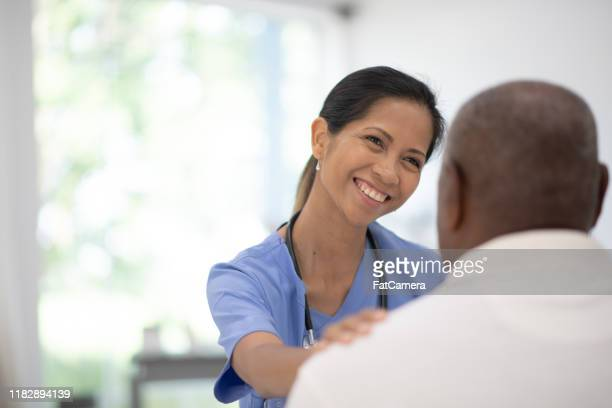 an elderly gentleman in his doctors office receiving a check-up stock photo - gerontology stock pictures, royalty-free photos & images