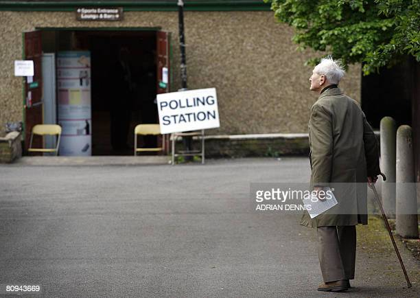An elderly gentleman stops to look at a bird while heading to cast his vote during the local elections at a polling station at Gunnersbury Triangle...