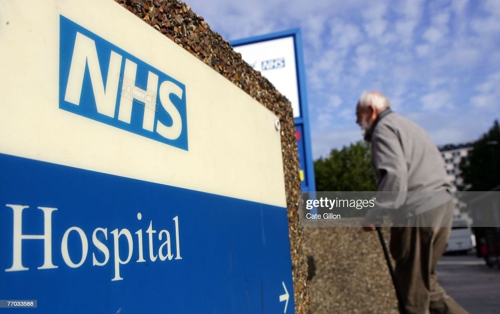 An elderly gentleman walks past a hospital sign on September 26, 2007 in London, England. In a report to be released September 27, 2007 the Healthcare Commission outlines care by the NHS Trust should provide further dignity in care to the elderly.